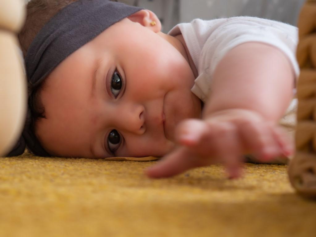 bébé qui attrape son doudou