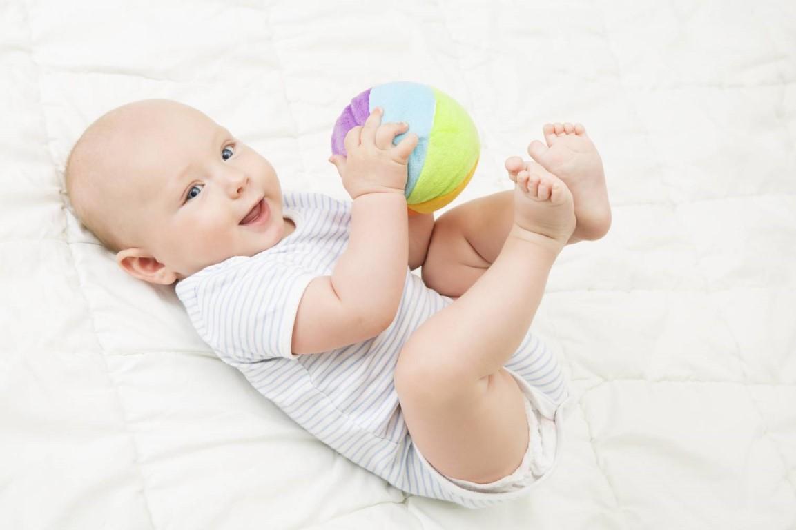 bébé qui joue avec une balle de prehension montessori